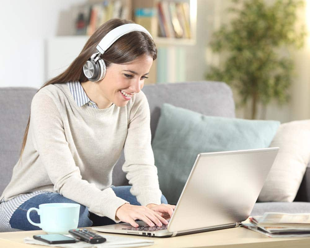 Happy girl e-learning with laptop and headphones